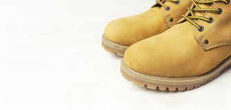 Free Close-up Yellow Men`s Work Boots From Natural Nubuck Leather On Wooden White Background. Trendy Casual Footwear Youth Style. Stock Photos - 155327443