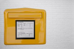 German mailbox on white brick wall. Close up of yellow metal German mailbox on outside of white brick house wall stock images