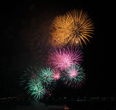 Close-up of yellow, pink and green fireworks display. Symbolizing New Year, celebration and pyrotechnics Royalty Free Stock Images