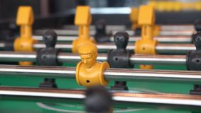 Young man playing enjoy foosball wooden table soccer game. Close-up yellow players, young man playing enjoy foosball wooden table soccer game stock footage