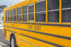 Close up of a yellow school bus on a snowy road against homes and cloudy sky. One of the windows of the bus functions as an emergency exit for the passengers stock image