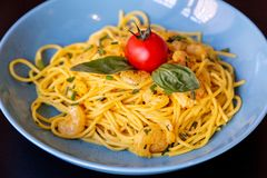 Close up of yellow spaghetti with prawns, a cherry tomato and basil royalty free stock images
