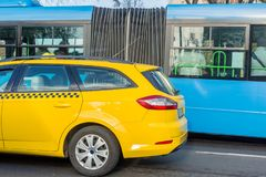 Close-up of yellow taxi near blue bus. Bus or taxi. City transportation and vehicle selection concept. Close-up of yellow taxi near the blue bus. Bus or taxi stock images