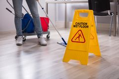 Close-up Of Yellow Wet Floor Caution Sign. Near Janitor Cleaning Office royalty free stock photography