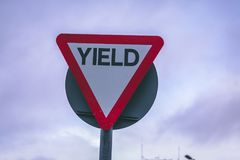 Close up of a yield road sign outside. Close up of a yield road sign on a cloudy day stock images