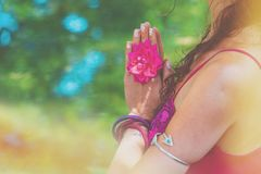Close up of yoga woman hands in namaste gesture with rose flower. Outdoor summer day light leak stock images