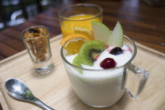 Close up of  yogurt pudding in a glass with fruits decorate,honey conflake in a mug shot,orange juice in a glass on wooden plate. Morning breakfast,diet and Royalty Free Stock Photo