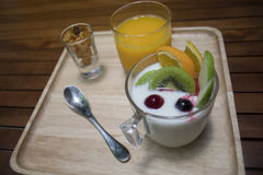 Close up of  yogurt pudding in a glass with fruits decorate,honey conflake in a mug shot,orange juice in a glass on wooden plate. Morning breakfast,diet and Stock Photo