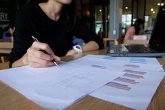 Close up of yong asian female business owner making calculations. Savings, finances and economy concept royalty free stock photos