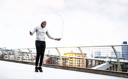 Young active black sportsman skipping with a rope in a city, wearing hoodie. A close-up of a young active black sportsman skipping with a rope in a city royalty free stock images