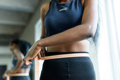 Close-up of young adult black woman in sports clothing. African american girl measuring waist with yellow tape close up Royalty Free Stock Photo