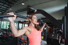 Close up young adult fitness woman doing pull ups. In pull up bar stock image
