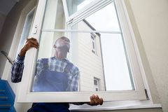 Handyman Installing Window. Close-up Of Young African Handyman In Uniform Installing Window stock photography