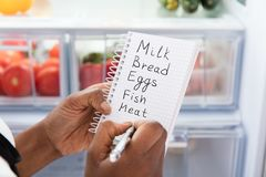 Woman Writing On Shopping List Near Refrigerator. Close-up Of Young African Woman Writing Shopping List Near Open Refrigerator royalty free stock photos
