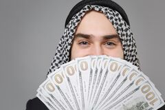 Close up of young arabian muslim businessman in keffiyeh kafiya ring igal agal isolated on gray background in studio