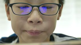 Close up of young asian boy playing games on smart phone with reflex blue box on glasses