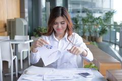 Close up of young Asian business woman tearing up charts on the desk in office Stock Photography