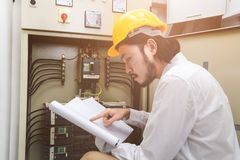 Engineer at work. Close up of young Asian electric engineer in beige pant and white shirt, wear yellow helmet, squat near control panel, working instruction in royalty free stock photography