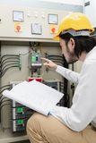Engineer at work. Close up of young Asian electric engineer in beige pant and white shirt, wear yellow helmet, squat near control panel, working instruction in royalty free stock photo