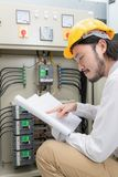Engineer at work. Close up of young Asian electric engineer in beige pant and white shirt, wear yellow helmet, squat near control panel, working instruction in royalty free stock image