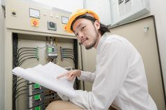 Engineer at work. Close up of young Asian electric engineer in beige pant and white shirt, wear yellow helmet, squat near control panel, working instruction in stock photos