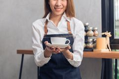 Close up of a young Asian female barista hold a cup of coffee serving to her customer with smile surrounded with bar counter. royalty free stock photos