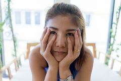 Close up Young Asian girl feeling bore looking through camera wi stock image