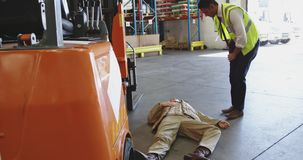 Accident in a warehouse loading bay 4k. Close up of a young Asian male warehouse worker jumping out a forklift truck to assist a colleague lying on the floor stock footage