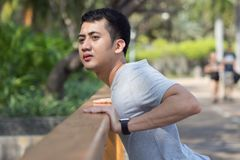 Young asian man warm down to calm their body by stretching his body after exercising at the park in a warm light afternoon. Close up of young asian man warm Royalty Free Stock Image