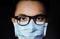 Close up of young asian man wearing hygienic mask and glasses royalty free stock photo
