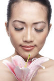Close-up of a young Asian woman holding a lily Royalty Free Stock Photo