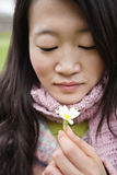 Close-up of a young Asian woman looking at flower Stock Photo