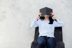 Close up of young asian woman reading book and hiding face on cement background. Girl leisure with activity, education concept Royalty Free Stock Photo