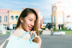 Asian woman shopping an outdoor flea market with a background of pastel bulidings and blue sky. Close up of a young Asian woman shopping an outdoor flea market Stock Image
