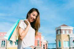 Close up of a young Asian woman shopping an outdoor flea market with a background of pastel bulidings and blue sky. Young woman smile with a colorful bag in Stock Photo