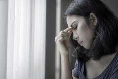 Asian woman suffering headache near the window royalty free stock image