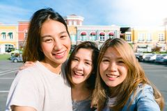 Close up of young Asian women group selfie themselves in the pastel buildings city in nice sky morning. City lifestyle of young women group on weekend. Outdoor stock photos