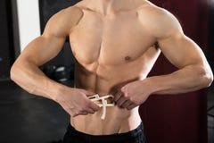 Person Measuring His Body Fat With Caliper. Close-up Of A Young Athlete Person Measuring His Body Fat With Caliper In The Gym Royalty Free Stock Photo