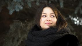 Close up for young, attractive girl in a fur coat and knitted scarf looking to the left in a winter park, street fashion royalty free stock photos