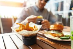 Close up of young attractive man eating french fries and burger at street cafe. stock images
