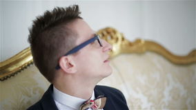 Close up. Young attractive man in glasses is sitting on a golden sofa and talking. stock video