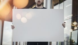 Close up of attractive man horizontally holding blank canvas at the street. royalty free stock photos
