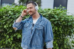 Close up of young attractive man listening to music on earphones in cityscape. stock photo