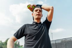 Close up of young man relaxing after tournament and holding tennis balls. royalty free stock image
