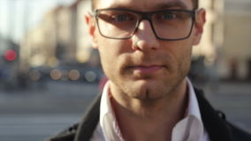 Close up of young attractive smiling man wearing eye glasess, outdoors. stock footage