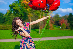 Close-up of young attractive woman in beautiful dress with red balloons Stock Images