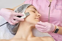 Close up of young attractive woman getting ultrasonic facial skin cleansing treatment by professional cosmetologist. Adorable stock image