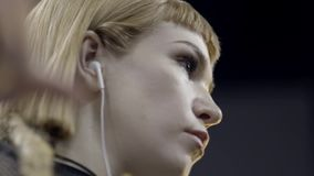 Close-up of young attractive woman listening to music with headphones. Action. Beautiful artistic young woman listening stock video