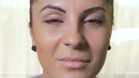 Close-up of young attractive woman opening eyes and smiling stock video footage