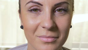 Close-up of young attractive woman opening eyes and smiling stock video